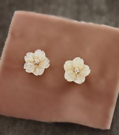 Beautiful hand-carved shell pearl flowers are adorned with a delicate rhinestone center to make these pretty stud earrings. These are even