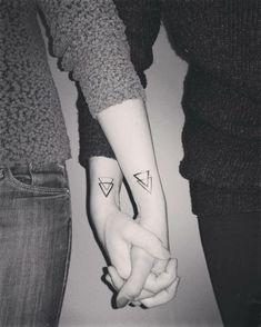tatuajes geométricos para hermanas o amigas, mujeres mano en mano, tatuaje en la muñeca triángulos entrelazados, foto en blanco y negro, mujeres con jersey