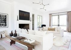 White living room with striped rug, wood console table, modern light fixture, and sheepskin rug under coffee table