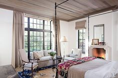 Andrew Fisher of Fisher Weisman created the Gleasons' bronze bed, which is draped with an antique suzani from Suzanne Tucker Home; the limestone mantel is by Atelier Jouvence. The love seat and wing chair are both by Summer Hill and the antique armchair is from Heather & Co.