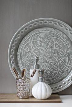 Zilveren schaal op kastje tegen de muur