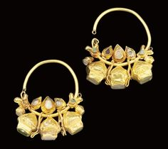 Seljuk / Selcuk Empire. Thick gold hoop earrings from 12th century Iran. They are thick gold wire, which ends in a dragon's head. The dragon's eyes are set with turquoise and the other stones are citrine. The earrings are 5cm high.