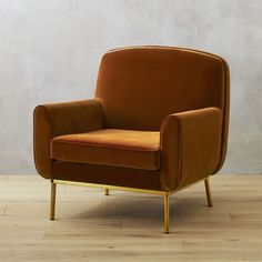 Shop halo orange velvet armchair.   Generous proportions play well with chic brass details by designer Caleb Zipperer.  Inspired by the 1970's living room of a childhood friend, white rounded seat rests atop brass-plated base and slender cylindrical legs.