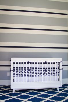 Painted horizontal stripes adorn an accent wall in this contemporary nursery, pulling together the room's crisp gray, blue and white palette. A graphic rug and chevron bedding layer in additional patterns for a high-contrast design.