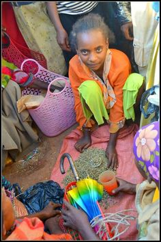 During weekend market days, children often help their parents at market. This 12 year old girl helps her mom sell coffee. Her mom, who has a Roots Ethiopia IGA, is happy to send this precious daughter to school. Her coffee sales makes it possible! To purchase her green coffee beans, you'd pay 3 birr for the small silver cup of beans, and 17 birr for the bigger orange cup of beans. Sponsor a child for school or a family with an income generating grant! www.rootsethiopia.org