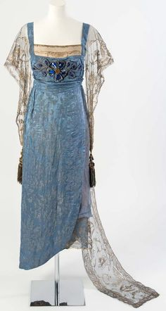 Lucile (Lucy, Lady Duff Gordon) Blue figured silk evening dress with gold net sleeves and train embroidered in gold metal strip and decorated with blue gems and tassels, 1911.Worn by Esme Giffard (née Wallace), daughter of Lucile, to celebrate the Coronation of King George V in 1911 and later altered for a Ball in 1919