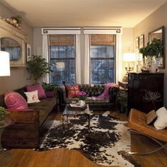 An eclectic living room with vintage furniture scores, a cow hide rug and custom window treatments & pillows.