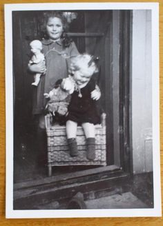 """""""Mamma had een fototoestel opgespaard van de sunlightzeep bonnen, geweldig! Nu foto's maken van de kinderen. De oudste met haar pop (geruild in de oorlog voor voedselbonnen) en de jongste met haar hondje op wielen. In de deuropening in de zon, een flitser was er natuurlijk niet. 1948."""" Ati #fotoschrijven"""
