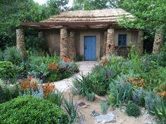 Zuid-Afrikaanse tuin (Lesotho) met bijpassend tuinhuis van leem, natuursteen en een palmbladeren dak.   Chelsea Flower Show 2015: 'Hope in Vulnerability'.  Ontwerp: Matthew Keightley