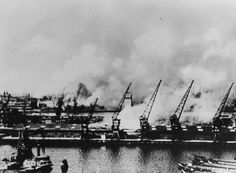 De Maashaven en Rijnhaven. Op de achtergrond de rook van de brandende stad, als gevolg van het Duitse bombardement van 14 mei 1940, links de torentjes van de Paradijskerk 14 of 15 mei 1940 GAR