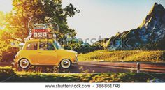 Cute little retro car with suitcases and bicycle on top goes by wonderful…