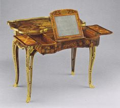 Madame de Pompadours dressing table.  Possibly made for Bellevue, it may appear in an image by J. Chauvet of her with her daughter, Alexandrine.  The coat of arms of the Marquise appears in the marquetry of the top along with her other interests; painting, music, architecture and gardening.  The table top slides back to reveal compartments for cosmetics and powders.  A mirror pops up to be utilized for the art of the toilette. Magnificent.