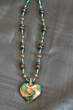 Trendy teal/green, gold and black necklace with larger glass heart pendant of same colors.  $20