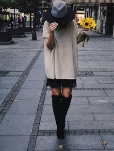 a chic way to style a lace dress when it's cold out - put a loose-fitting, long sweater over the top! Finish with high boots.