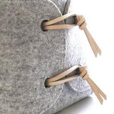 Caja de almacenaje elegante juguete suave con detalles de cuero. La canasta es extremadamente versátil y puede ser utilizada para cualquier cosa, desde juguetes a ropa. Se muestra aquí en gris claro o blanco con cuero natural lazos pero también está disponible en carbón. Si usted