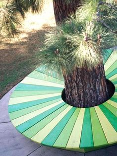 """BHG: Dont Forget Paint, a backyard wooden bench built around the base of a tree and """"painted alternating shades of jungle green, chartreuse, and yellow-green."""" Sounds to me like a fun, family project for the weekend or short holiday!"""