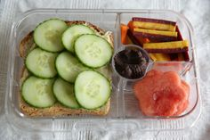 Yumbox Panino with hummus cucumber sandwich, flower watermelon slices, carrots and a peanut butter chocolate cup.