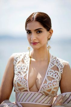 Sonam Kapoor showing in a laser-cut blouse and a ruffled white Abu Jani Sandeep Khosla saree at Cannes 2015.