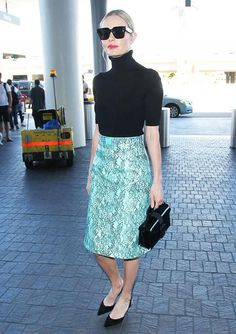 Kate Bosworth wears a printed skirt with a black turtleneck and black pointed toe heels.