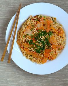 Kimchi Scallion Noodles    Serves 2 as part of a multi-course meal, or 1 hungry person as a main course    1 tablespoon smooth peanut butter  2 tablespoons water  1 tablespoon soy sauce  2 teaspoons sesame oil  1 teaspoon sugar  3 scallions, white and green parts separated and thinly sliced  2 cloves garlic, minced  1/4 cup kimchi  2 packs instant ramen, flavor packets discarded  1 small handful of peanuts, chopped