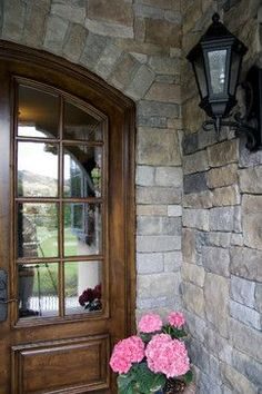 traditional English cottage stone entryway and wood front door with window panes, wrought iron sconce, pink peonies House Paint Exterior, Exterior House Colors, Exterior Design, Stone Veneer Exterior, Stone Facade, Outdoor Fireplace Plans, Limestone House, Eldorado Stone, Traditional Exterior