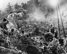 Weary after a third night of fighting against North Vietnamese troops, U.S. Marines crawl from foxholes located south of the demilitarized zone (DMZ) in Vietnam, 1966. The helicopter at left was shot down when it came in to resupply the unit. Photo by ©Henri Huet