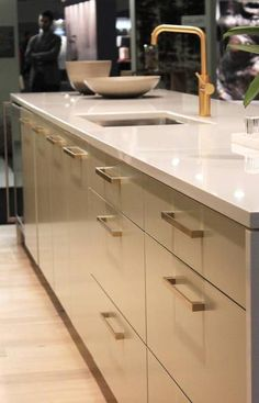 The key to having gold, the colour (which isn't always the metal we call brass), work gloriously is to use it sparingly. This show kitchen features a custom-built a brushed-bronze hood fan, plated hardware in brushed brass, and a beautiful brass faucet. (Rosa Pearson)
