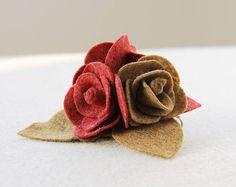 Spilla con rose in pannolenci e feltro rosso scuro e marrone.