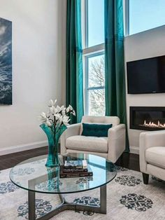 Turquoise Floor To Ceiling Drapes Accentuate The Tall And Windows In This Contemporary Living Room A Wall Fireplace Warms Up Adds Ambiance