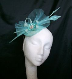 Aqua Arrow Feather & Crinoline Bow Galaxy Fascinator Mini Hat Order Now from www.indigodaisyweddings.co.uk Specialising in stunning bespoke cocktail fascinators and formal hats in a wide range of colours, perfect for Royal Ascot and The Kentucky Derby. Plus all your wedding floral accessories including shoe clips, vintage flapper bands, feather and flower fascinators, feather fans, fairy wands, wrist corsages, wedding bouquets & buttonholes. Worldwide Delivery.