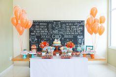 Mesa de doces com tema raposa, com lousa ao fundo com informações do aniversariante, balões de gás e toalha cinza chevron. Foto: Juliana Laporta Fotografia