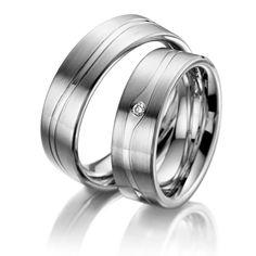 Eheringe ars amandi aus Edelstahl, Breite: 7,00 - Höhe: 2,50 - Steinbesatz: 1 Brillant 0,03 ct. tw, si (Ring 1 mit Steinbesatz, Ring 2 ohne Steinbesatz). Alle Eheringe können Sie individuell nach Ihren Vorstellungen konfigurieren.