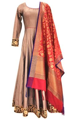 This set features a grey fully flared and pleated floor length suit in silk base with resham thread embellished border around the hem and cuffs. It also features a sheer back and hot pink dori tie up with metallic silver tasseled hangings. The contrast banarasi silk dupatta truly enhances the beauty of the outfit. It comes with a matching churidar pants. Get your hands on this magnificent creation and look utterly elegant. Note: The design of the banarasi dupatta may change based on…
