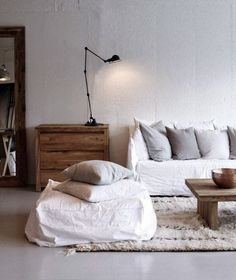 white boho minimal living room with rustic wooden accents | white linen sofa and pouf / ottoman | Want the Ghost Gervasoni sofa without spending top dollar? Update an IKEA Söderhamn sofa with a Bemz Loose Fit Urban cover in Absolute White Rosendal Linen
