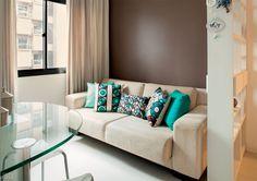 """Cores escuras em pontos estratégicos também são bem-vindas. Nas paredes atrás do sofá e da cama, o tom da tinta (Marrom Autêntico, ref. 60YR 09/086, da Coral) aquece o espaço. A mesa de refeição, também com desenho da arquiteta, tem base de alumínio e tampo de vidro para conferir leveza (Simone Capato Vidros, R$ 900). """"O principal desafio, ao elaborar o projeto de um apartamento pequeno, é otimizar o espaço sem poluir o visual"""", conta. Projeto de Andrea Del Monaco."""