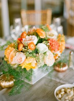 weathered wooden boxes filled with ranunculus, dahlias, and about 15 other flowers for the table centerpieces, switched out with glass cylinders filled with sand and topped with succulents and orange pincushion protea. i also incorporated the gold & copper sprayed pumpkins throughout the reception