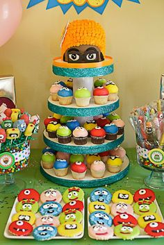 Katie Grace Designs: AMAZING Yo Gabba Gabba Party! Love the DJ Lance cupcake stand topper! The cake pops are awesome! and the dipped character pretzels are adorable! There are popcorn cones and cookies! And I love the idea that it doesn't have to be Christmas to have some candyncanes!