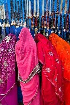 Colorful sari-clad Rajasthani women shopping at the Pushkar Camel Fair in India.