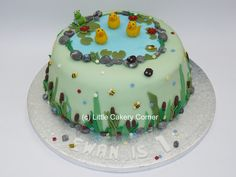 The cutest little duck pond cake ever!  After hours of painstakingly hand-making the details, a beautiful scene has come together!  This little boy's 1st birthday cake features ducks, lily pads, a friendly frog, ladybirds, tiny buzzy bumble bees, bull rushes, reeds, pebbles, grass and small blossom flowers.  This would also be lovely as a little girl's birthday cake or little boy's birthday cake for any age.