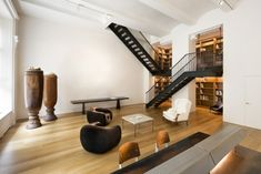 Selldorf Architects merged two apartments on New York's Upper East Side with this pair of black staircases. The pair of urn-like sculptures echo its duality, as do the sets of chairs, lamps, and wall of bookshelves.