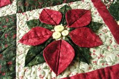 """""""Poinsettia"""" is a Christmas quilt pattern like no other. The dimensional petals and leaves radiate and point to the other flowers as they interplay with the Chr"""