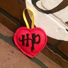 What better way to show your Christmas tree some HP love. Hand embroidered on felt then lovingly sewed and stuffed this Potter inspired heart ornament would look great on any geek's tree. Due to the handmade nature of our accessories, no two ornaments will be exactly the same. Stickers i...