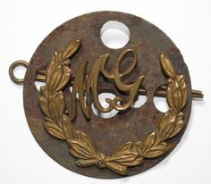 This is an original British gilding metal arm badge of being the Machine Gunner, consisting of the letters 'MG' with its 2 original rear loops in a wreath also with its 2 original rear loops. Its all got its original tin backing plate and split pin. British Army, World War I, Wwi, Badges, Arms, Plate, Military, Letters, Wreaths