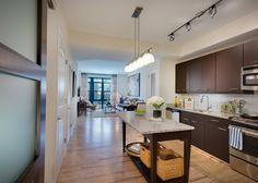Serious cooks with appreciate Flats at Bethesda Avenue apartments' gourmet, chef-inspired kitchens with GE stainless steel appliances, granite countertops, full-tile backsplashes, and movable furniture-style kitchen islands.