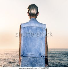 girl in stylish denim outfit sea background sunset