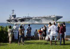Friends and family greet the aircraft carrier USS John C. Stennis (CVN 74) as it arrives at Joint Base Pearl Harbor-Hickam for a port visit.