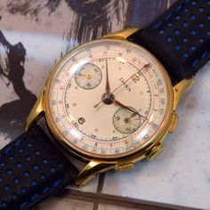A 1950s Doxa Yellow Gold-filled 2 Register Chronograph watch with a patinated silver dial with a black minute track, a red telemeter track and a blue tachometer track. Doxa was a Swiss watch manufacture that was founded in 1889 and in the 1960s began to emphasize production on diving watches, their Doxa SUB, a stalwart model in their collection. (Store Inventory # 9731, listed at $1750). (at Second Time Around Watch Company - Vintage Watches)