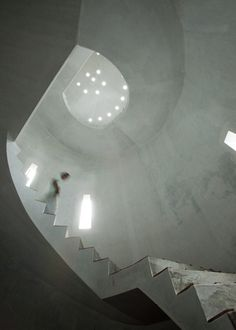 A concrete staircase spiralling up through an empty tower