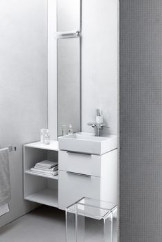 GREY BATHROOM The rigid geometry of the ceramic items is tempered by the multicoloured lightness of the transparent plastic elements. Leaving aside primary colours Kartell by Laufen sets coloured light horizons into the free area of the house where the senses yield to the emotions