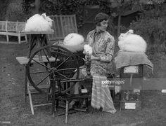 Sybil Mary spinning Angora rabbit wool in her garden. 1930